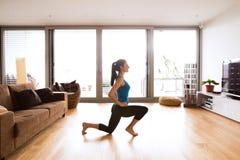 Giovane donna che si esercita a casa, allungando le gambe Fotografia Stock