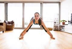 Giovane donna che si esercita a casa, allungando le gambe e armi Fotografie Stock