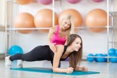 Giovane donna che si esercita con il suo istruttore di forma fisica Fotografia Stock Libera da Diritti