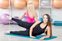 Giovane donna che si esercita con il suo istruttore di forma fisica Immagine Stock Libera da Diritti