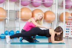 Giovane donna che si esercita con il suo istruttore di forma fisica Immagine Stock