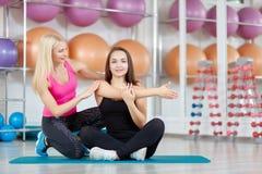 Giovane donna che si esercita con il suo istruttore di forma fisica Immagini Stock Libere da Diritti