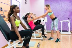 Giovane donna che si esercita durante l'allenamento del gruppo in una forma fisica moderna Fotografia Stock Libera da Diritti