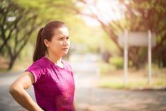 Giovane donna che si esercita nel parco riscaldamento per correre fotografie stock