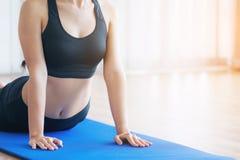 Giovane donna che si esercita nella palestra dell'interno sulla stuoia di yoga Immagine Stock Libera da Diritti