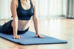 Giovane donna che si esercita nella palestra dell'interno sulla stuoia di yoga Fotografie Stock Libere da Diritti