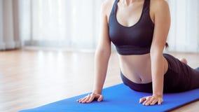 Giovane donna che si esercita nella palestra dell'interno sulla stuoia di yoga Immagine Stock