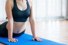 Giovane donna che si esercita nella palestra dell'interno sulla stuoia di yoga Immagini Stock Libere da Diritti