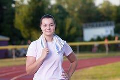 Giovane donna che si esercita su una pista all'aperto Immagine Stock Libera da Diritti