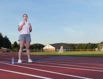 Giovane donna che si esercita su una pista all'aperto Fotografie Stock
