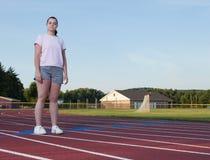 Giovane donna che si esercita su una pista all'aperto Immagini Stock