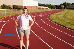 Giovane donna che si esercita su una pista all'aperto Immagini Stock Libere da Diritti