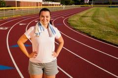Giovane donna che si esercita su una pista all'aperto Fotografia Stock