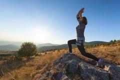 Giovane donna che si esercita sulla montagna sul campo idilliaco al tramonto Fotografia Stock Libera da Diritti