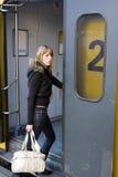 Giovane donna che si imbarca su un treno immagini stock