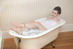 Giovane donna che si inzuppa in vasca antica immagine stock libera da diritti