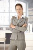 Giovane donna che si leva in piedi in braccia dell'ufficio attraversate Fotografie Stock Libere da Diritti