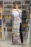 Giovane donna che si leva in piedi con la grande pila di libri Fotografia Stock
