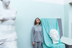 Giovane donna che si leva in piedi contro una parete Immagine Stock