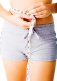 Giovane donna che si misura su bianco Fotografie Stock Libere da Diritti