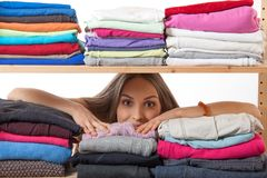 Giovane donna che si nasconde dietro uno scaffale con abbigliamento immagini stock