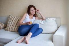 Giovane donna che si rilassa a casa con un vetro di succo d'arancia immagini stock