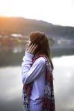 Giovane donna che si rilassa in cielo di alba di estate all'aperto Immagine Stock