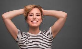 Giovane donna che si rilassa con le mani dietro la testa su fondo grigio immagini stock