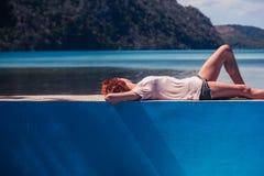 Giovane donna che si rilassa dalla piscina Immagine Stock