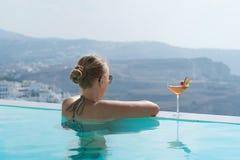 Giovane donna che si rilassa nello stagno con una vista splendida su Santorini fotografia stock