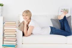 Giovane donna che si rilassa su un sofà Fotografie Stock Libere da Diritti