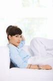 Giovane donna che si rilassa su un sofà Fotografia Stock