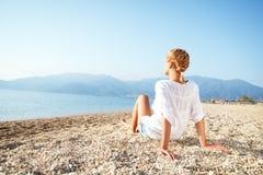 Giovane donna che si rilassa sulla spiaggia di mattina Fotografia Stock