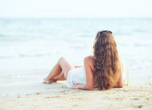 Giovane donna che si rilassa sulla spiaggia nella sera Fotografia Stock Libera da Diritti
