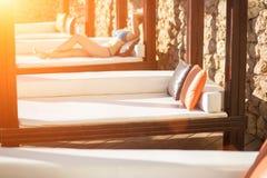 Giovane donna che si rilassa sullo sdraio dalla piscina alla località di soggiorno Chiarore di Sun Immagine Stock