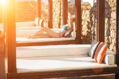 Giovane donna che si rilassa sullo sdraio dalla piscina alla località di soggiorno Chiarore di Sun Fotografie Stock