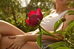 Giovane donna che si rilassa in una sedia di salotto nel suo giardino, vicino ad un bello fiore della peonia, fuoco selettivo fotografia stock libera da diritti