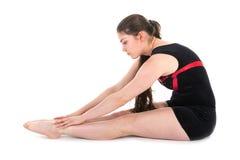 Giovane donna che si scalda per un esercizio relativo alla ginnastica Isolated a bianco Immagine Stock Libera da Diritti
