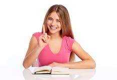 Giovane donna che si siede ad una tabella Immagini Stock Libere da Diritti