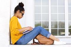 Giovane donna che si siede all'aperto e che legge un libro Fotografia Stock