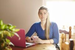 Giovane donna che si siede alla tabella con il computer portatile che sembra preoccupato Fotografie Stock Libere da Diritti