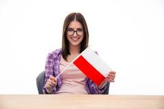 Giovane donna che si siede alla tavola con la bandiera polacca Fotografie Stock Libere da Diritti