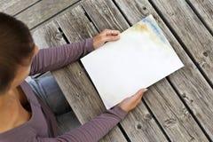 Giovane donna che si siede alla tavola di legno con un libretto con la copertura bianca Immagini Stock