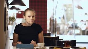 Giovane donna che si siede in caffè con il cuscinetto e bere archivi video