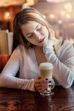 Giovane donna che si siede in caffè con la tazza di coffe fotografia stock