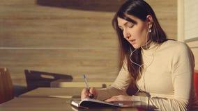 Giovane donna che si siede in caffè con le cuffie e che fa le note in taccuino Fotografia Stock