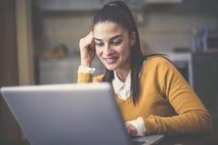 Giovane donna che si siede a casa e che lavora al computer portatile fotografie stock