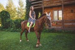 Giovane donna che si siede a cavallo, passeggiata nella natura Fotografia Stock
