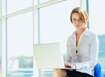 Giovane donna che si siede con il computer portatile fotografie stock