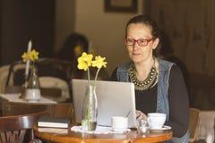 Giovane donna che si siede con il computer portatile alla tavola in un caffè freelancer Fotografia Stock Libera da Diritti